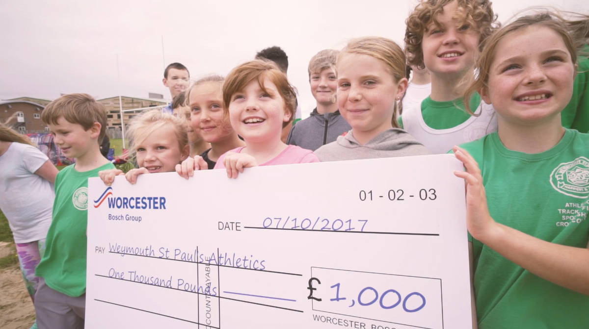 Young Weymouth athletes holding their cheque