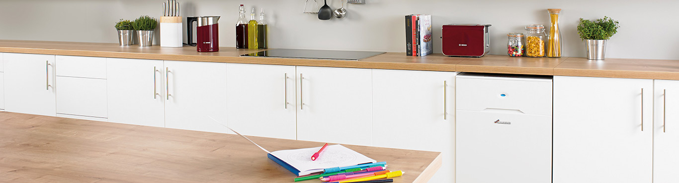 Photo of a kitchen countertop with a notepad and colourful pens.