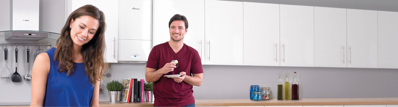 Photo of a couple in a kitchen where a man is eating a cupcake with a grin on his face.