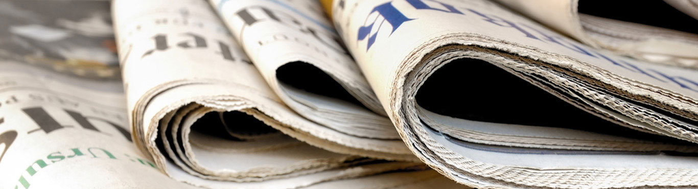 Closeup photo of newspapers stacked.
