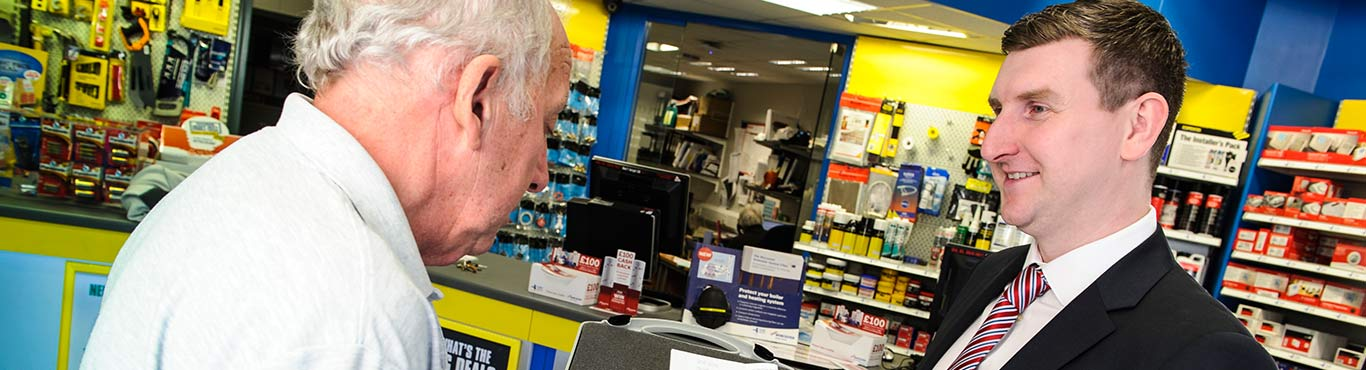 Photo of shop owner explaining a product to a customer.