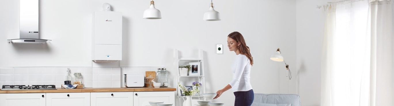 Photo of couple in a kitchen talking, with a boiler.Lady in Kitchen with boiler